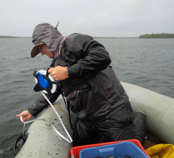 CNSC staff measuring depths for fish nets near McClean Lake